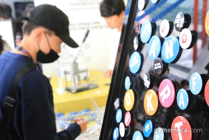 정성스레 배지를 고르고 있는 관객들 (사진: 게임메카 촬영)